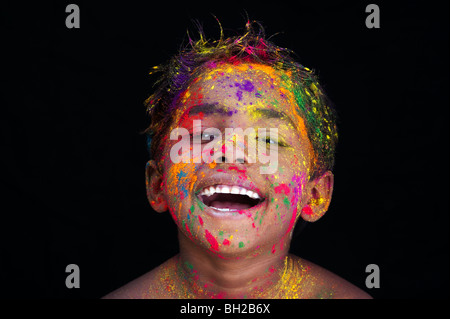 Happy young Indian boy covered in coloured powder pigment against a black background. India - Stock Photo