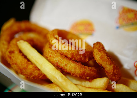 Typical New York Cheese burger, also know as Hamburger with Cheese, french fries, Coke and onion rings - Stock Photo