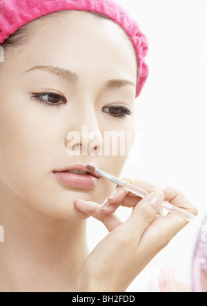 A young woman having makeup on - Stock Photo