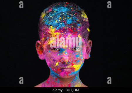 Serious young Indian boy covered in coloured powder pigment against a black background. India Stock Photo
