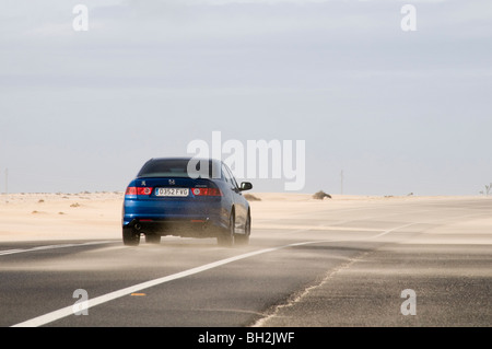 desert road roads sand sandy road slippery surface surfaces driver driving in on dust dusty wind swept blown across - Stock Photo