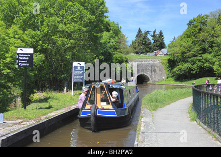 A narrowboat coming from Chirk Tunnel on to Chirk Aqueduct where the Llangollen Canal crosses the English/Welsh - Stock Photo