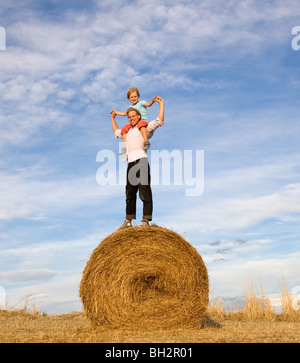 man and boy standing on hay bale - Stock Photo