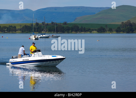 Two men in a motor boat on Midmar dam, Midlands, Kwazulu Natal, South Africa. - Stock Photo