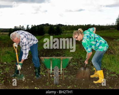 Man and woman shoveling dirt - Stock Photo