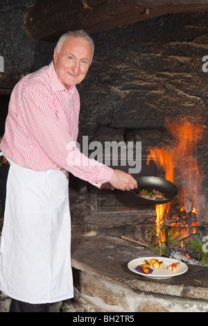 elderly cook by fireplace serving food - Stock Photo