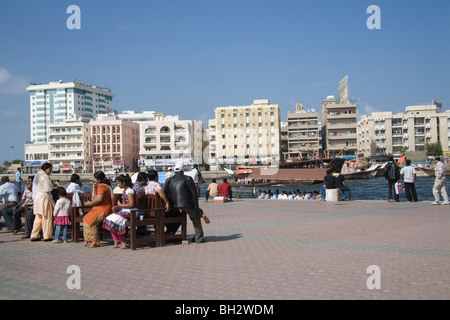 Dubai United Arab Emirates Group of Indians sitting outside in the sunshine on wooden benches with views across - Stock Photo