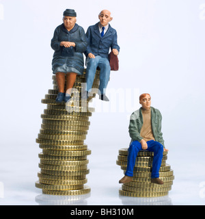 Old and young figures sitting on coins - inheritance / disparity in savings / pension money / old v young income - Stock Photo