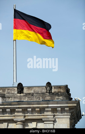 German flag on the top of one of the Reichstag towers, Berlin, Germany - Stock Photo