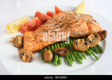 A meal of pan-fried salmon steak with steamed asparagus, fried mushrooms and fresh tomatoes - Stock Photo