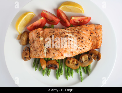 looking down on a plate of pan-fried salmon fillet served on a bed of asparagus with tomatoes and mushrooms - Stock Photo
