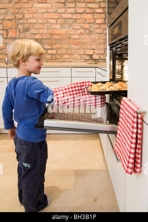 boy taking baked cookies from oven - Stock Photo
