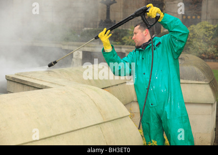Man using a steam jet washer to clean masonry. - Stock Photo