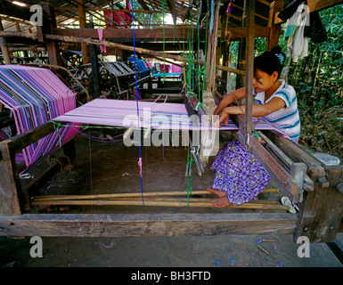 Young Kayin girl weaving traditional pattern on a loom Junge Karen Frau webt traditionelle Muster Myanmar Burma - Stock Photo