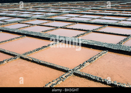 salt pan pans saltpan saltpans evaporation of sea water to leave salt dry drying rock road salt fuerteventura canary - Stock Photo