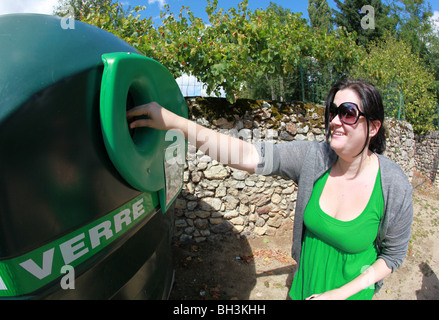 People recycling glass bottles, France. - Stock Photo