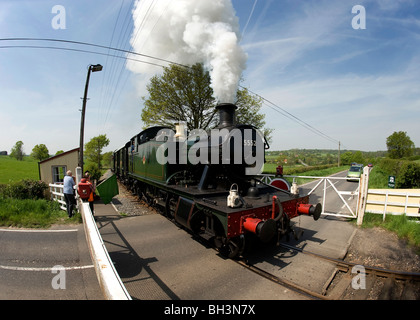 A steam train on the Kent and East Sussex railway crosses over the Cranbrook Road crossing, 5th May 2008. - Stock Photo