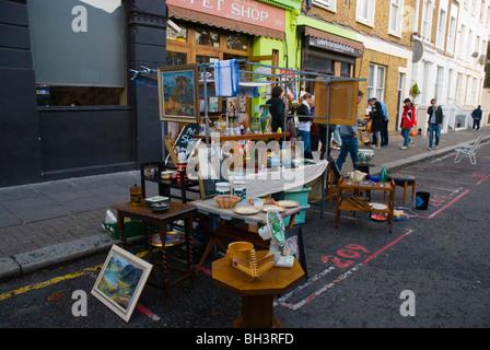 Stall selling second hand goods Portobello Road market London England UK Europe - Stock Photo