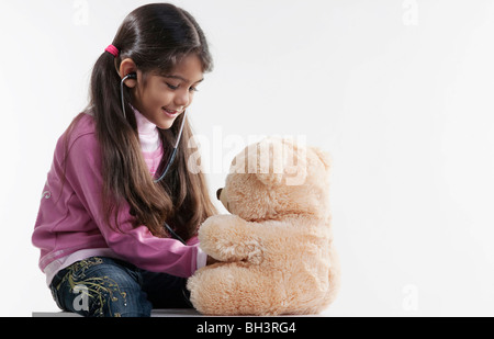 Girl playing with a teddy bear - Stock Photo