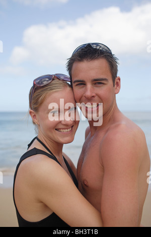 Young couple embracing on beach, smiling - Stock Photo