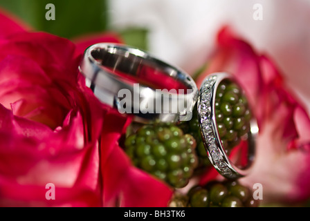 Wedding rings sitting on a bouquet of flowers. - Stock Photo