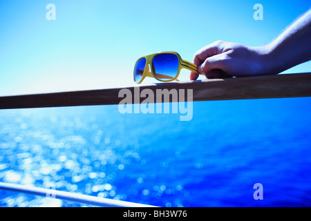 A man's hand holding on to a pair of retro yellow sunglasses resting on a wooden handrail on a cruise ship against - Stock Photo
