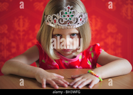 Young girl wearing a red dress and a Princess crown sitting at a table, frowning with a miserable expression - Stock Photo