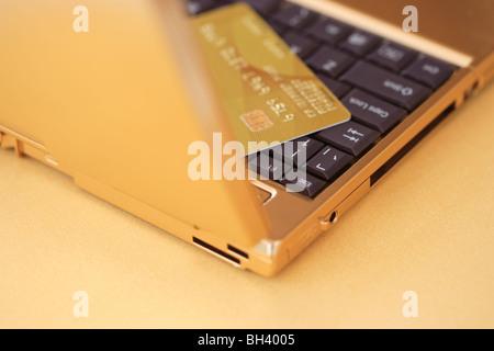 A golden laptop computer and a golden credit card on a golden desk - Stock Photo