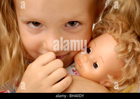 Expressive closeup portrait of a little girl with a doll - Stock Photo