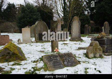 A cross in a graveyard in WInter - Stock Photo
