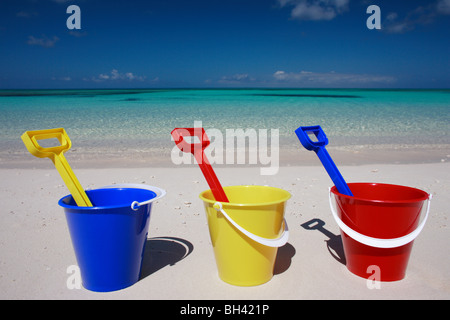 Three toy buckets and spades in a line on a tropical beach - Stock Photo
