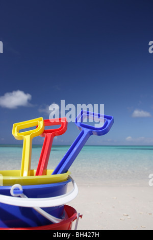 Three children's toy buckets and spades on a deserted tropical beach - Stock Photo