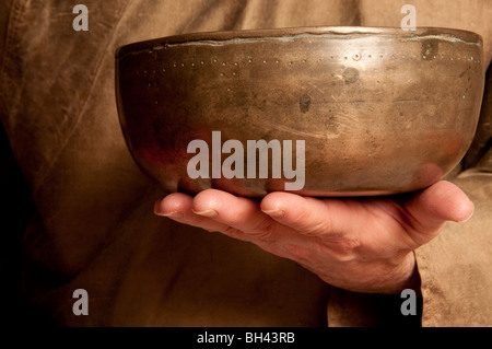 Tibetan singing bowl being held up in front of healing sound practitioner chest - Stock Photo