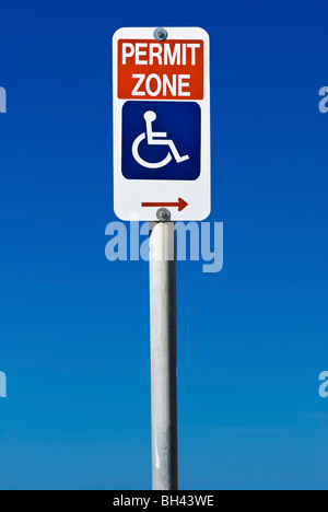 A sign indicating disabled permit parking only isolated on a blue graduated sky background. - Stock Photo