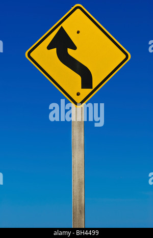 A road sign indicating a bend in the road. Isolated on a graduated blue background. - Stock Photo