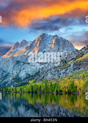 Silver Lake reflection with fall colored cottonwood trees and sunrise. California. Sky has been added. - Stock Photo