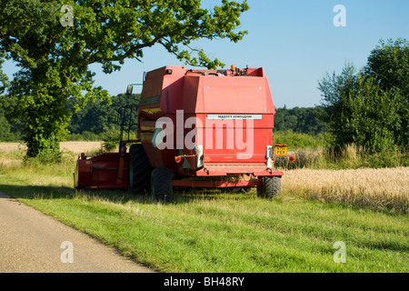 Combine waiting to get to work on Norfolk farm in July. - Stock Photo