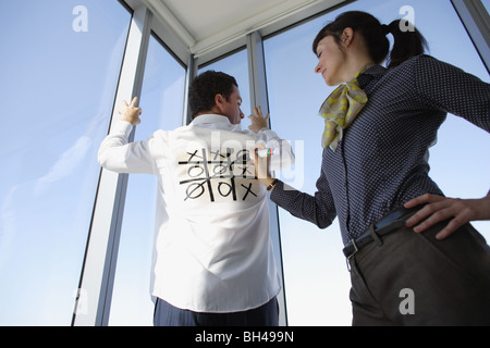 A woman playing Noughts and Crosses ( Tic Tac Toe ) on the back of a man's white business shirt - Stock Photo