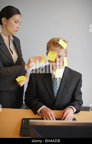 A businesswoman placing sticky notes of paper on to a businessman's face as he sits at a desk working on a computer - Stock Photo