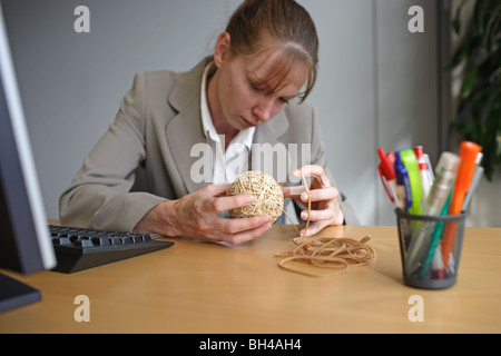 A businesswoman making a rubber band ball at an office desk with an expression of concentration - Stock Photo