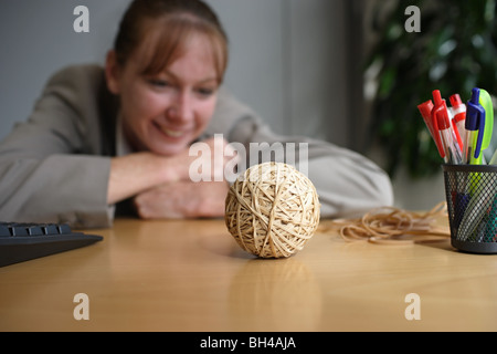 A businesswoman looking at a hand made rubber band ball on an office desk, smiling - Stock Photo