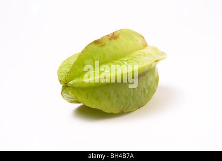 Unripe Asian Star Fruit isolated against white background. - Stock Photo