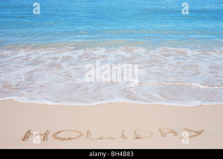 The word 'Holiday' written in the sand on a tropical beach - Stock Photo