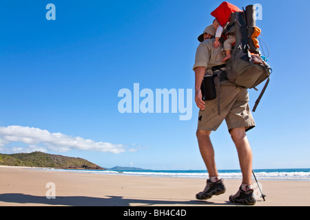 A man hikes while carrying his baby in Zoe Bay, Hinchinbrook Island, Queensland, Australia. - Stock Photo