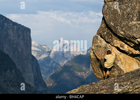 With Half Dome and El Capitan in the background, a young man is seen bouldering in Yosemite Valley, California. - Stock Photo