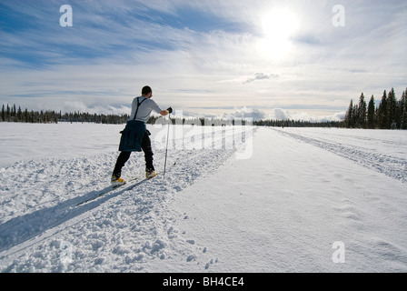 A young man cross country skis on a snowy trail in Safari Lake, Alaska. - Stock Photo