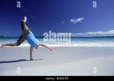 Young man performing a cart wheel on a deserted tropical beach - Stock Photo