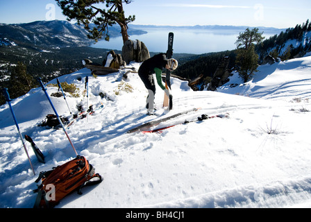 A young man takes the skins off his skis in preparation of skiing in the backcountry in Incline Village, Nevada. - Stock Photo