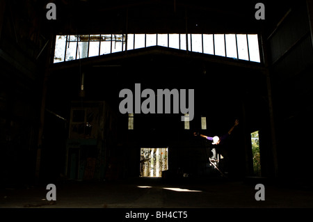 A skater ollies in an abandoned warehouse on the Central Coast, New South Wales, Australia. - Stock Photo