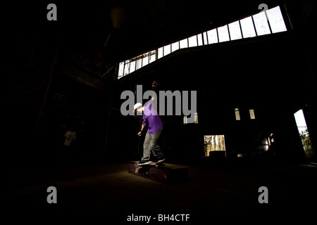 A skater performs a smith grind at an abandoned warehouse on the Central Coast, New South Wales, Australia. - Stock Photo
